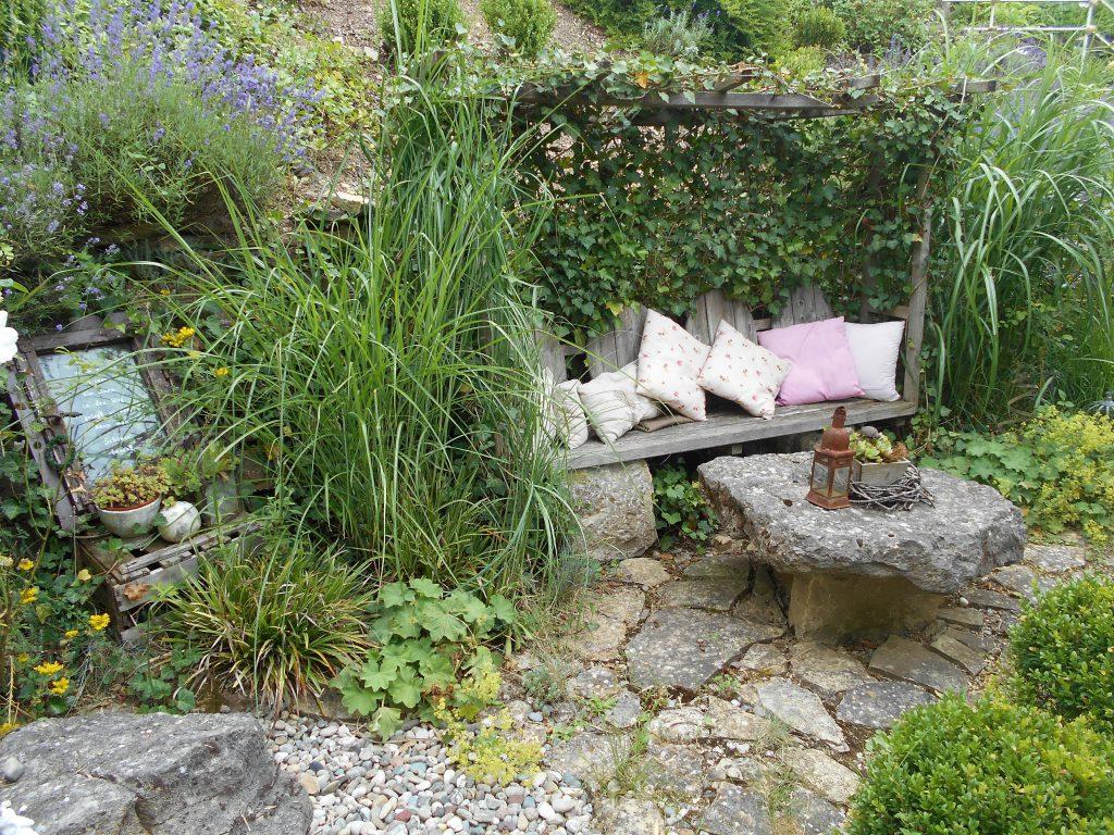 """Elke und Markus Hartmann aus Gissigheim genießen ihr Gartenidyll: """"Vor 10 Jahren haben wir unseren großen Garten nach und nach angelegt. Wir geniessen mit unseren drei Kindern Kristin, Silas und Jana jede freie Minute im Garten. Vor allem abends kann man in aller Stille auf der aus Efeu umrankten Bank ein Buch lesen."""""""